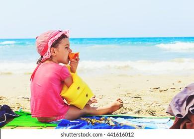 cute toddler eating fresh summer peach  on the beach