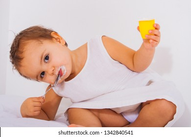 Cute Toddler eating some yoghurt in a white dress