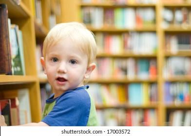 cute toddler explores the bookshelves