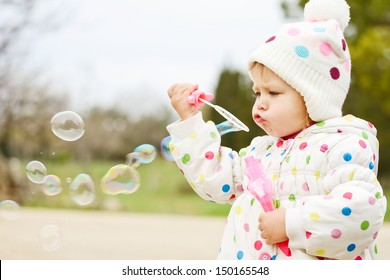 cute toddler girl blowing   soap bubbles
