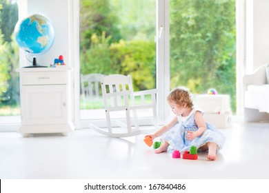 Cute toddler girl with curly hair wearing a blue dress playing in a white sunny bedroom with a big window with garden view