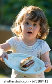 Cute toddler girl eating hot dog hotdog