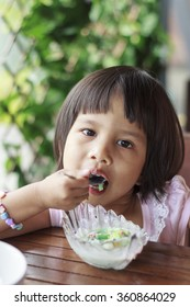 Cute Toddler Girl Eating Ice-Cream on a spoon