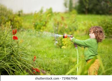 Cute toddler girl having so much fun watering flowers in the garden.