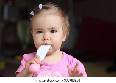 Cute toddler girl with her first hairstyle gnawing the comb, indoor portrait