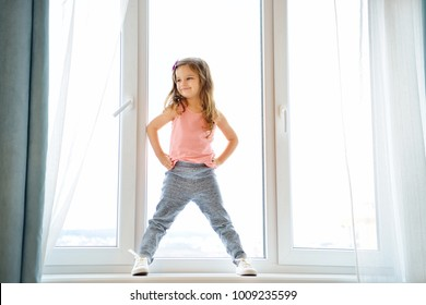 Cute toddler girl at home in white room is standing near window. The beautiful kid on windowshel. Child with curly hear is looking at camera.