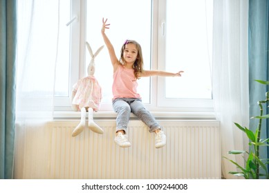 Cute toddler girl at home in white room is sitting near window. The beautiful baby girl with toy rabbit sitting on windowshel. Baby with curly hear is looking at camera.