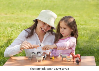Cute toddler girl and mom play with farm animal figures outdoors. Summer vacation childhood in the countryside. The child learns farm animals. Early education and development