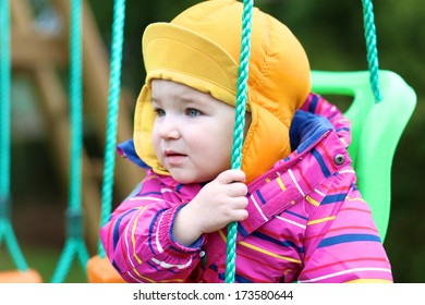 Cute toddler girl in multicolor jacket and orange hat rocking outdoors on the swing