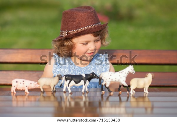 Cute toddler girl playing with farm animal figures outdoors. Summer leisure. childhood on countryside. Child learning farm animals. Early education and development. Role-playing with animals