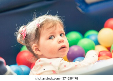 Cute toddler girl playing on indoor playground.