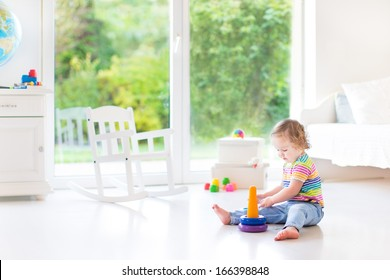 Cute toddler girl playing with a pyramid toy in a white room with a big window with garden view