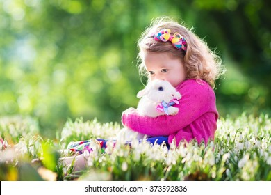 Cute toddler girl playing with real rabbit in blooming spring garden. Child on Easter egg hunt. Kid with colorful eggs and pet bunny. Kids play with pets. Children feeding animal. Family with animals.
