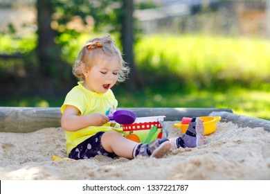 Cute toddler girl playing in sand on outdoor playground. Beautiful baby having fun on sunny warm summer sunny day. Happy healthy child with sand toys and in colorful fashion clothes.