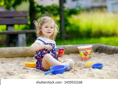 Cute toddler girl playing in sand on outdoor playground. Beautiful baby in red trousers having fun on sunny warm summer day. Child with colorful sand toys. Healthy active baby outdoors plays games