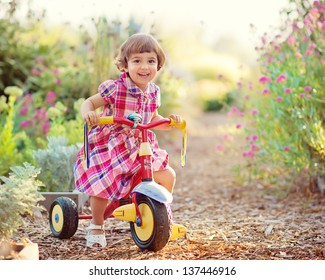 Cute Toddler Girl Riding Tricycle