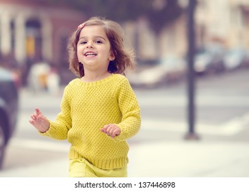 Cute Toddler Girl Running in the City