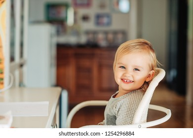 Cute toddler girl sitting at the desk, ready to draw