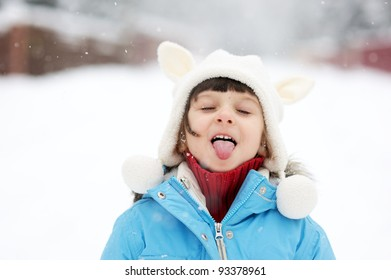 Cute toddler girl in snowsuit posing outdoors on bright winter day