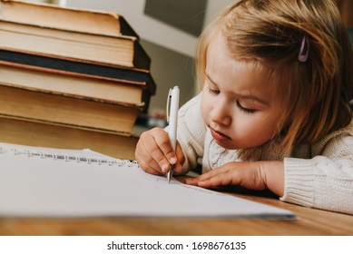 Cute toddler girl surrounded by books learns to write. Concept of development, training and education