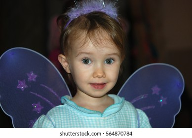 Cute toddler girl in violet wings
