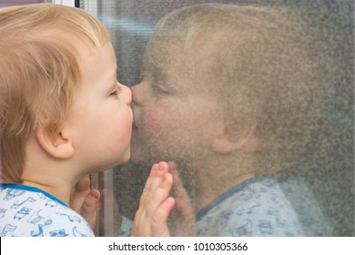 Cute toddler leaning to the window and kissing his reflection in the mirrow.