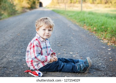Cute toddler on  summer landscape, sitting and smiling