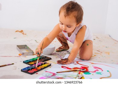 Cute toddler painting with watercolors her hands and feets