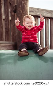 Cute toddler playing slide at playground