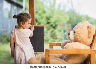 Cute toddler playing teacher role game outdoors. Little child drawing with pieces of chalk on a blackboard. Happy kid leaning letters and numbers. Children education concept