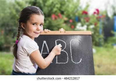 Cute toddler playing teacher role game with her Teddy bear friend outdoors. Happy kid leaning letters Children education concept