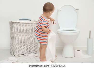 Cute toddler playing with toilet paper in bathroom