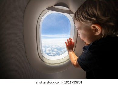 cute toddler points his finger at the sky through the window. first flight concept, traveling with children