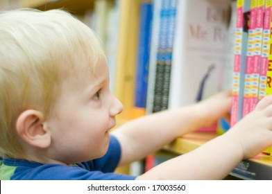 cute toddler reaches for books on a shelf