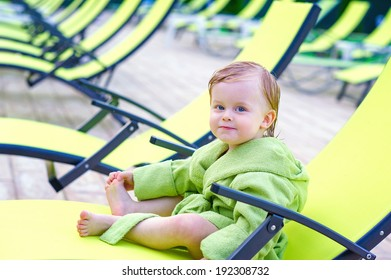 Cute toddler sitting on a lounge chair in the bathrobe after swimming and posing