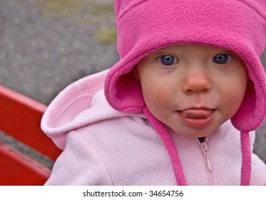 A cute toddler is sitting on a red park bench, with a pink outfit on and has her tongue out in this candid real life shot.