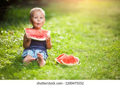 Cute toddler sitting outdoords and eating a slice of watermelon