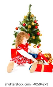 Cute toddler sitting under Christmas tree and opening her present