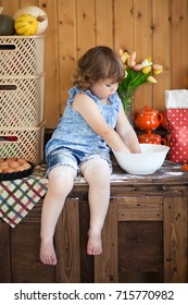 Cute toddler smiling kid in the rustic kitchen indoors. Baking sweet apple cake and having fun. Flour dirty hands. Homemade food.Little mothers helper
