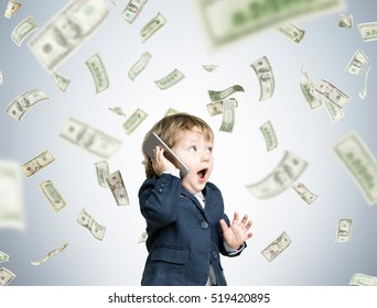 Cute toddler wearing a suit and talking on his smartphone is standing under a dollar rain in a gray room