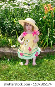 cute toddler in  a yellow sun dress wearing a big floppy straw hat