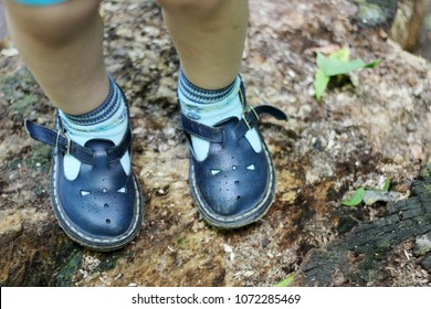 Cute toddlers feet in retro shoes over natural ground, fashion and beauty concept, retro style