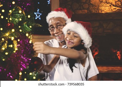 Cute toothless little girl and her grandfather decorating a Christmas tree while wearing Santa hat at home
