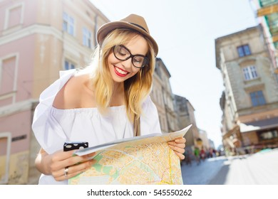 Cute tourist girl with light hair and red lips wearing hat and glasses, holding map and mobile phone at old European city background and smiling, sunny weather, portrait.