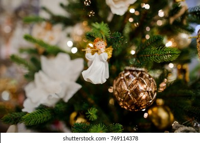 Cute toy angel with a flute and fir cone hanging and decorating a Christmas tree