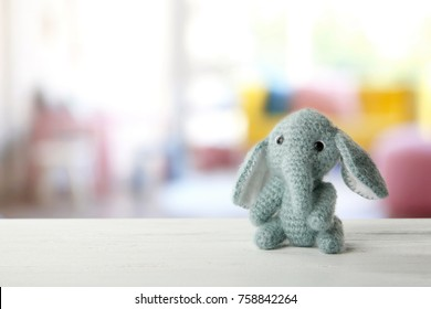 Cute toy and blurred interior of children room on background
