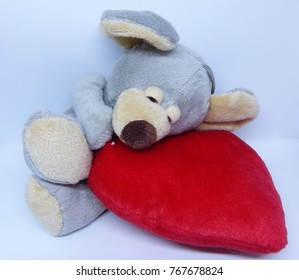 Cute toy grey  mouse sleeps on red pillow on white background, Valentine present, love and happiness