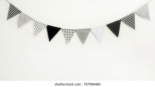 Cute triangle bunting flag gray, white, black color polka dot, plaid, striped pattern design hanging for party decorated on wall room with copy space for text.birthday or festival concept