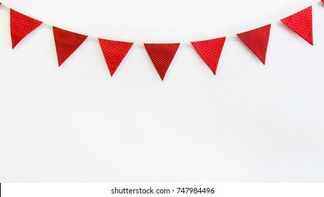 Cute triangle bunting flag red, white, black color polka dot, plaid, striped pattern design hanging for party decorated on wall room with copy space for text.birthday or festival concept