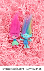 cute trolls on pink abstract paper background. hasbro trolls. concept of children's games, fun, toys.